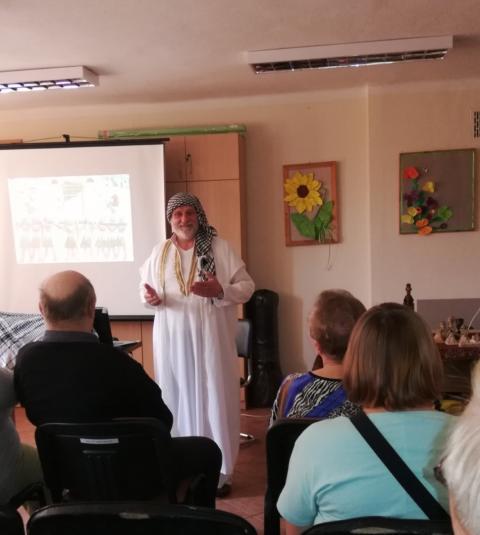 Pan Grzegorz Królicki w oryginalnym stroju egipskim prezentuje uczestnikom Środowiskowego Domu Samopomocy zdjęcia przedstawiające egipskie zabytki.